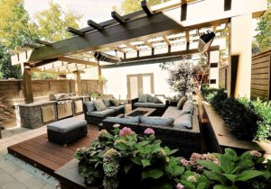 alt=raised planters wrap around a ground level deck that has an arrangement of outdoor furniture centred on a fire table | a pergola overtop spans the full width of the backyard with outdoor heaters suspended above the deck and a roof over an outdoor kitchen
