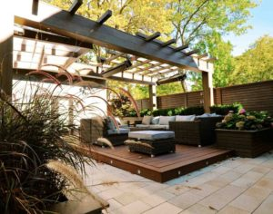 alt=deck podium clad in tropical hardwood   outdoor furniture arranged around a fire table   suspended has heaters   ornamental grass in foreground planter