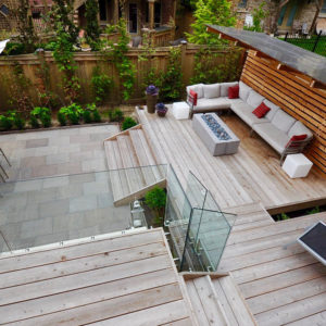 Looking down onto upper balcony with glass railing to lower deck sectional and fire table beneath a cantilevered roof surrounded by plantings