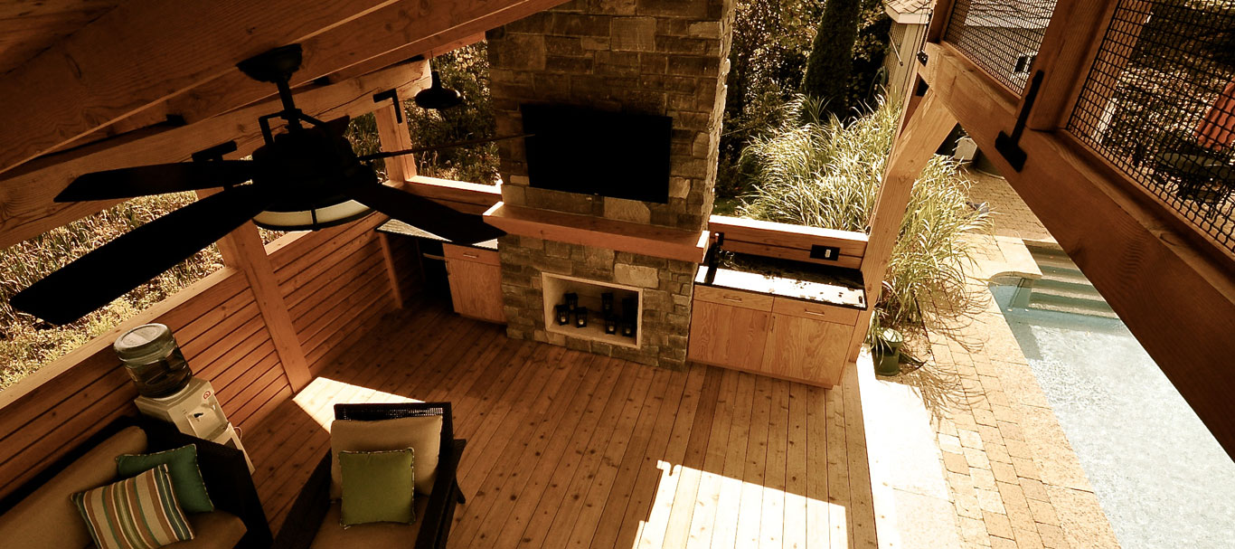 View inside pavilion from above down to stone veneer fireplace between wood cabinets with black countertops alongside a swimming pool