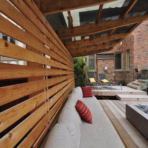 A white couch with colourful pillows positioned against a horizontal wood privacy screen beneath cantilevered rafters supporting a plexiglass roof