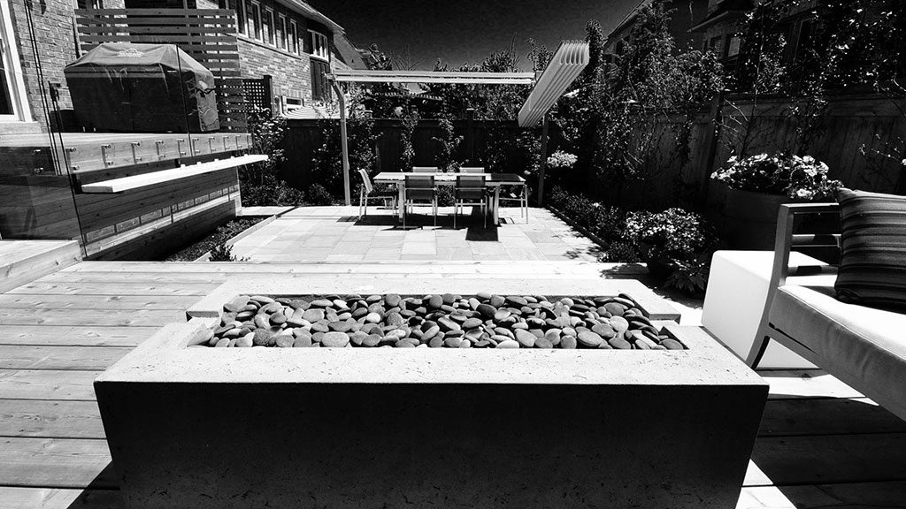 Foreground view of Fire Table on Deck Looking Down on Patio to Dining Table and Modern Umbrella.