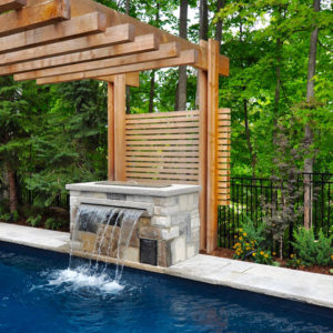 A close up view of a sheer decent stone-clad swimming pool fountain with a horizontal wood screen backdrop spanning the pergola end posts.