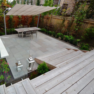 View looking down from deck to flagstone patio with its border plantings against the fence and a Tdining table beneath modern umbrella.