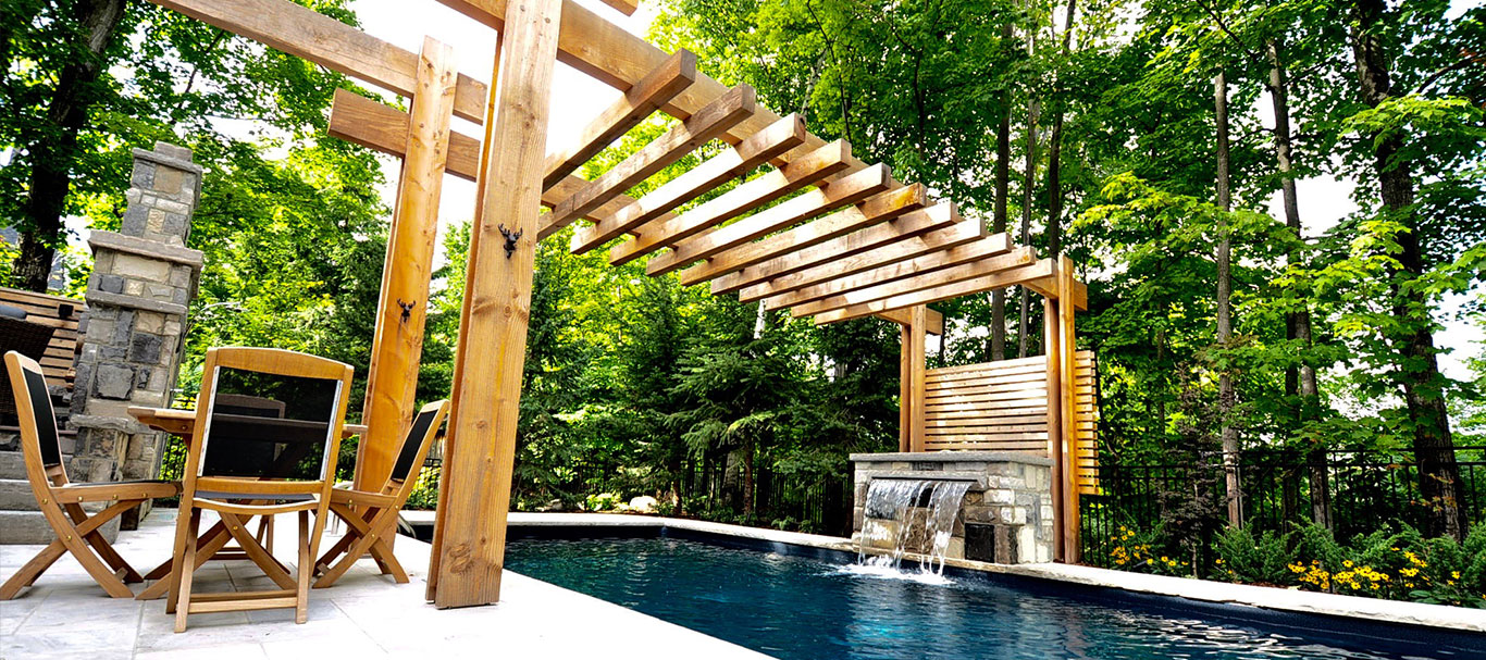 Stone pool deck teak table chairs beneath pergola. Lush forest in background. timber pergola spans width swimming pool the posts framing a stone fountain spilling in pool.