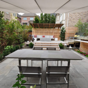View from behind dining table with overhead umbrella towards deck with wide steps and sectional couch beneath cantilevered roof.