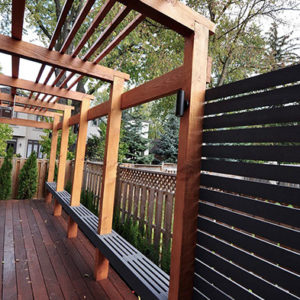 View looking down one half of an Ipe deck with a modern pergola overhead with linear purlins. The posts with built-in floating bench recede in the distance.