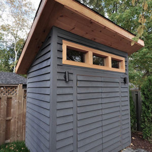 A modern garden shed set in the corner of a backyard has a slanted roof allowing for a transom window above the double doors with shiplap siding.