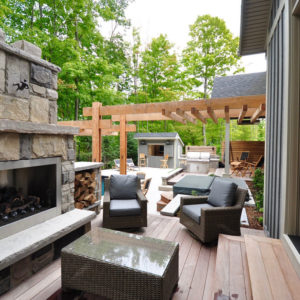 Down steps from bedroom door, a cozy deck with furniture arranged in front of stone clad outdoor fireplace. Woodland background with cabana.