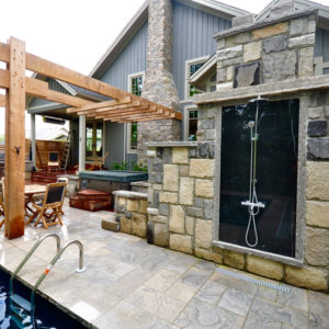 The backside of outdoor freestanding fireplace has a wall mounted shower with a polished faux black granite monolithic panel inset.