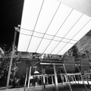 Garden patio dining furniture beneath a modern dual post umbrella it's fabric a bright white in the sunlight
