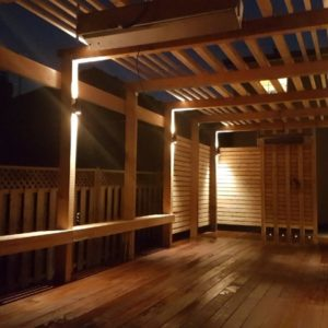 2-way cylinder lights mounted on deck pergola posts cast light down onto the floating bench and up to linear purlins creating a magical effect.