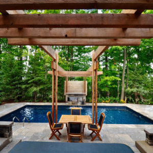 Spa and table and chairs align beneath pergola terminating at fountain on other side of swimming pool.