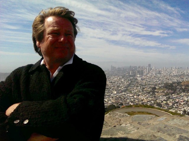 Photo of man with arms crossed, his face in shadow faces camera standing on a hill with downtown San Francisco in the background.