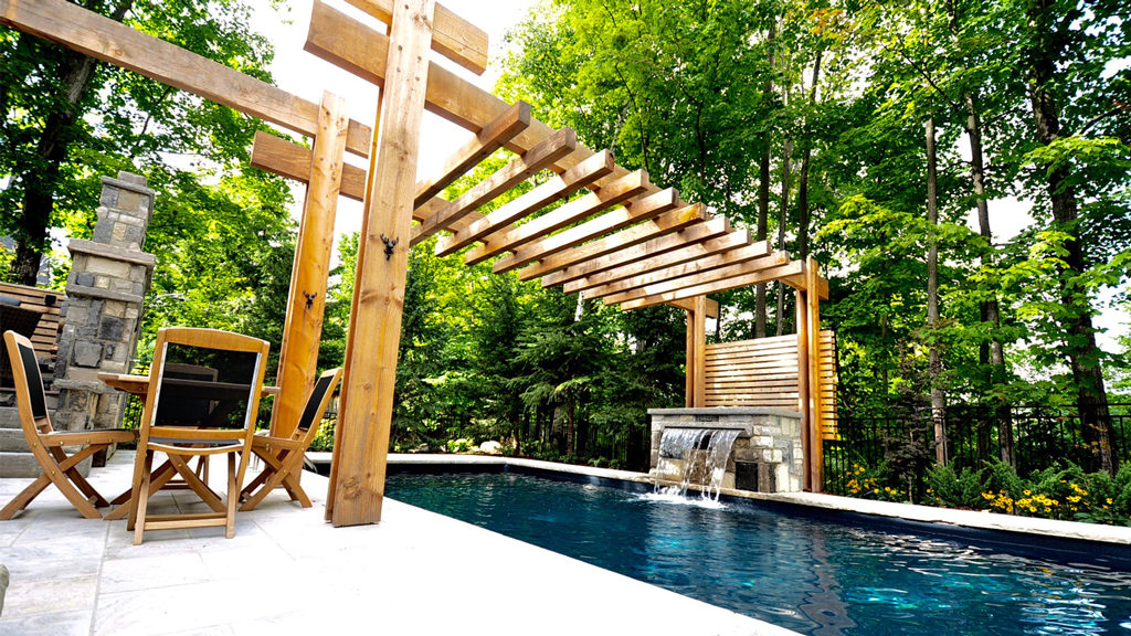 Stone pool deck teak table chairs beneath pergola. Lush forest in background. timber pergola spans across middle of swimming pool.