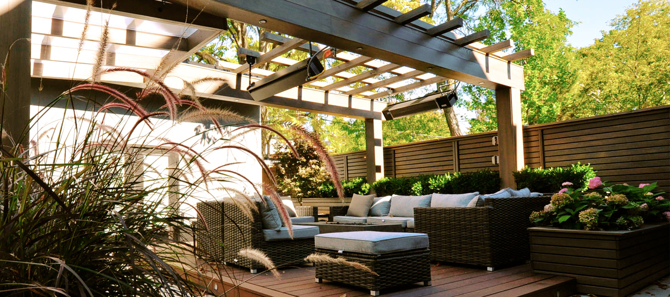 City garden between laneway garage and house has lounge furniture arranged on a ground level deck set beneath a dramatic pergola that spans width of the yard.