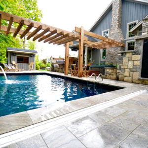 A wet sawn limestone pool deck in foreground, outdoor shower in corner, outdoor kitchen and spa between pool and back of house. Cabana at end of pool.