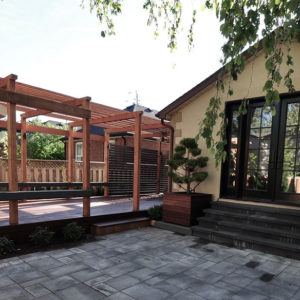 A row of Hydrangeas and a square planter box separate the long deck and pergola from the walkout patio.