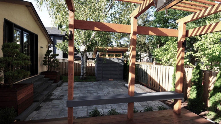 A view from deck through pergola posts to a walkout patio with a modern shed roof shed in the back corner.