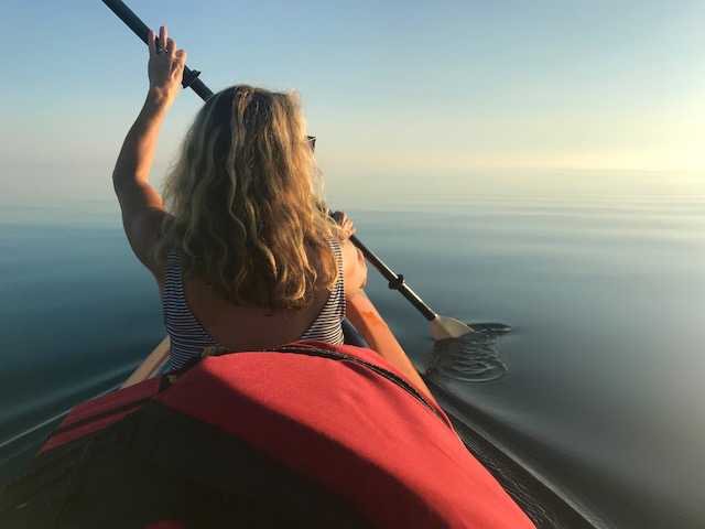 Looking from behind, a woman with long blond hair dips her kayak oar into glassy still water that continues to the horizon.