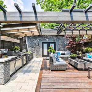 outdoor kitchen and lounge area beneath common pergola