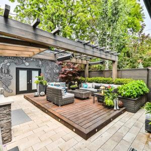 Backyard deck podium lounge enveloped by raised planter