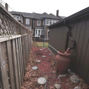 Before photo of narrow space between garage and fence.